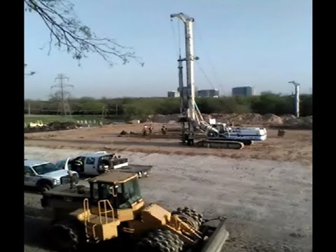 Giant 50 Foot Tall Auger Drill Pier Drilling Rig on Construction Site
