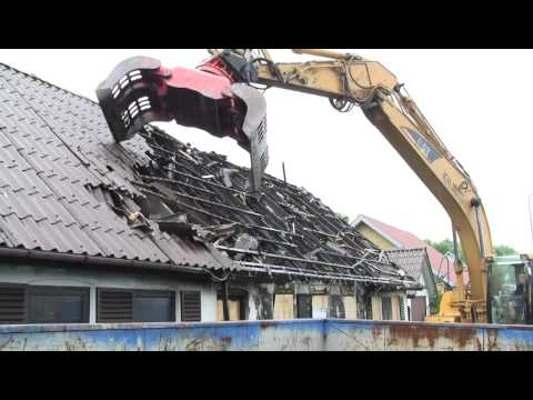 Tearing Down The Roof Sheeting On A Burned House