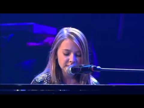 A Young Girl Plays The Piano And Sings