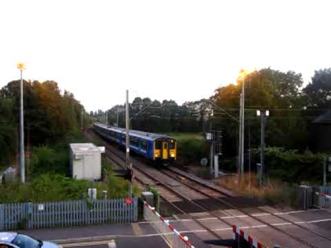 An eight-car formation of two Class 317s arrives at St. Margarets on the Hertford East branch, with one carriage starting to show the rainbow on its' livery ...