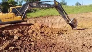 Escavadeira volvo 140 carregando e fazendo acabamentos