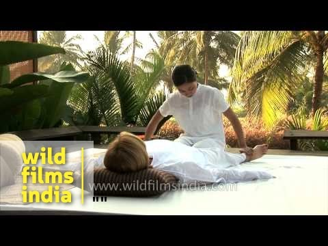 Girl gives foot massage to a tourist at a resort in Goa