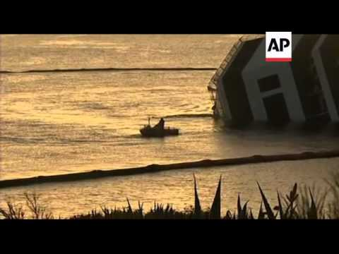 Tug boats lay new boom around stricken cruise liner; sunrise pix of wreck