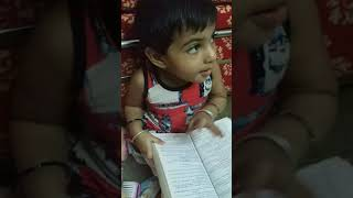 Funny baby reading a book