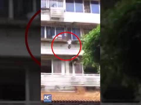Boy hanging on window railings rescued by passers-by