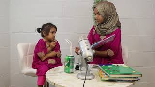 Better Quality: Fatima [2 yrs] is telling a story to Maryam Masud