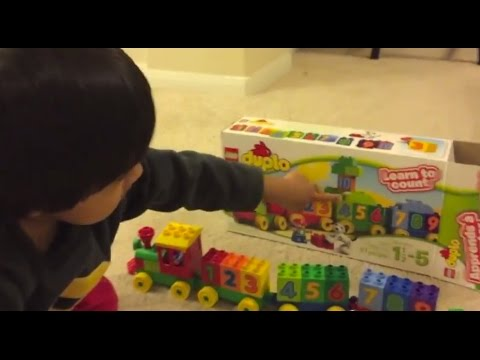 Kid playing with toys Lego Duplo Number Train