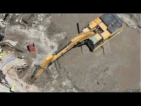 Cat 345DL Excavator digging in extreme mud