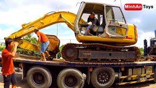 Excavator climbing onto Truck: Excavator and Dump Truck Loading Digging Transporting Mud