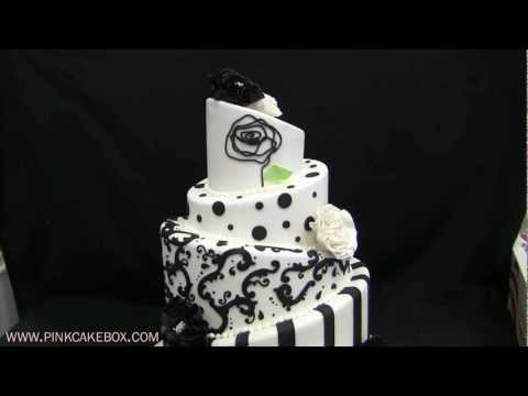 This wedding cake is colored in black and white and is topped with a