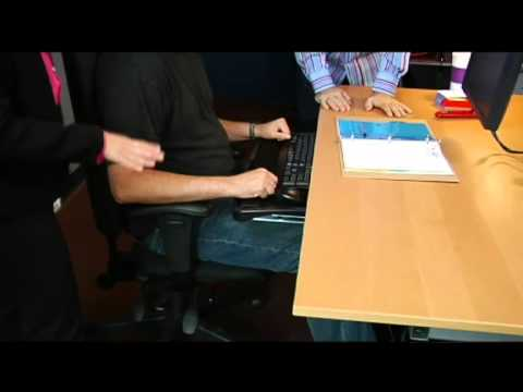 Mandy Gallant, from Ergo Risk, and Mike Agerbo, host of GetConnectedTV, assist Brian Ahlf position his adjustable Kensington SmartFit® desk accessories to achieve maximum productivity and...
