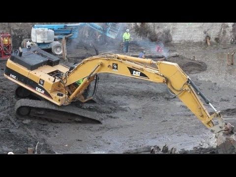 Cat 345CL Excavator digging dirt from around sheeting