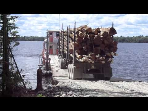 2013 loaded logging truck driving on to barge on Moosehead Lake, Maine