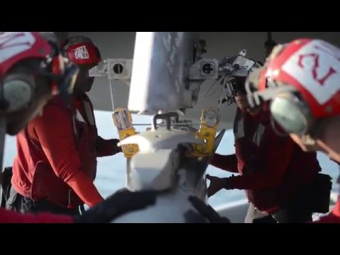 USS Harry S. Truman ordnancemen load bombs onto F/A-18 strike fighters for missions against ISIL