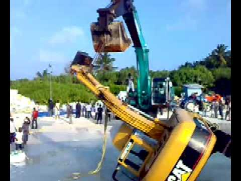 Excavator accident in the sea Caterpillar Crash in the sea on Maldive islands on the beach crane