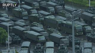 China conducts drills near Hong Kong border, stations dozens of paramilitary vehicles nearby