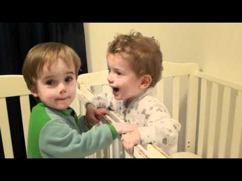 Twin Toddlers Kissing each other goodnight.