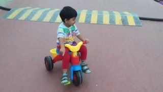Baby riding tricycle.