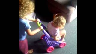 Summer pushing Caitlin in a toy stroller