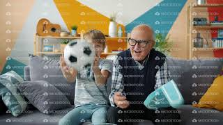 Portrait of excited people grandfather and grandson watching football on TV cheering
