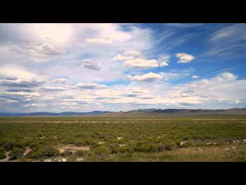Time-lapse of grassy plain and clouds landscape.