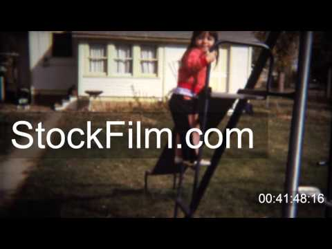 1971: Cute caucasian toddler girl goes down backyard steel slide. BOULDER, COLORADO