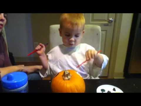 Micah paints a pumpkin
