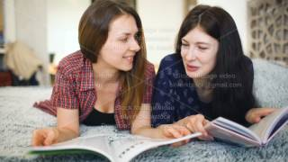 Two young woman friends are watching magazine on bed in bedroom at home