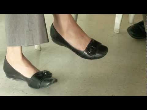 Candid woman shoeplay and dangle wearing black flats