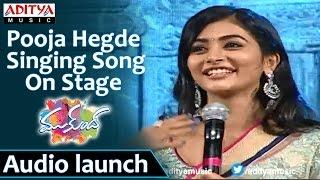 Pooja-Hegde-Singing-Song-On-Stage-At-Mukunda-Audio-Launch-Varun-Tej,-Pooja-Hegde