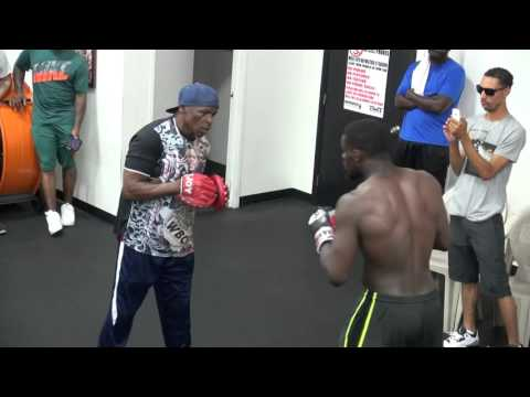 Andrew Tabiti and Floyd Mayweather working pads inside the Mayweather Boxing Club