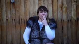 Thick woman smokes on the street.