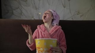 Woman Watching a Late Night Movie at TV, Eating Popcorn. Bathrobe, Facial Mask | Stock Footage -
