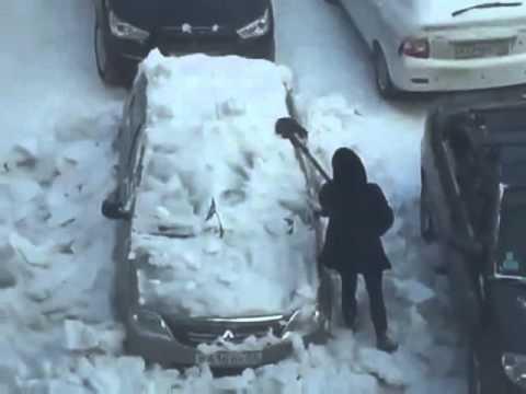 Девушка чистит свой автомобиль металлической лопатой