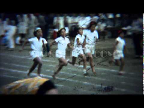 1961: Asian schoolgirl foot race running track white uniform event. TOKYO, JAPAN