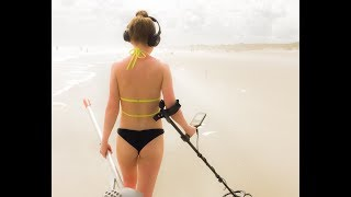 Girl metal detecting on the beach
