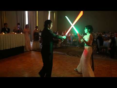 Bride and Groom simulating a lightsaber duel at their wedding
