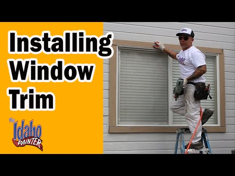 Installing New Window Trim On The Exterior Of A House.
