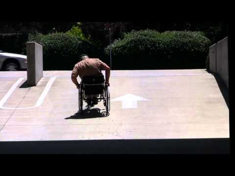 Rio Mobility Dragonfly attachable hand cycle exiting on a steep ramp