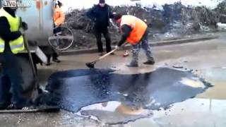 Road repair work in Russia  Asphalt on the water