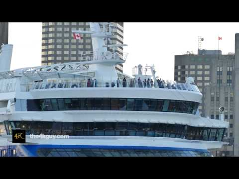 4K UHD - Tourists on cruise ship's top level deck with buildings in background