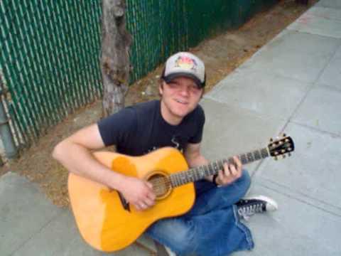 Ben Kasica playing guitar on the sidewalk
