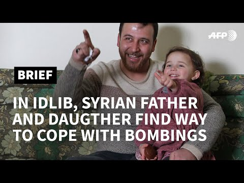 Syrian father and three-year-old daughter laugh off the shelling | AFP