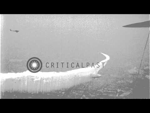 Skywriting airplane welcomes Graf Zeppelin by encircling it with heavy vapor trai...HD Stock Footage