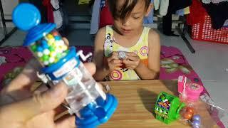 Tina mở quà ba tặng. Kẹo bồn cầu. Son môi ăn được. Máy loto quay trúng thưởng, kẹo singum mỹ. Usa