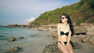 Young sexy woman in sunglasses smiling and sitting on rock at beautiful tropical beach