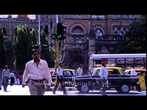Man crossing a busy road of Mumbai in front of Brihanmumbai Municipal Corporation