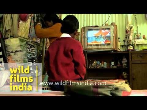 Assamese boy watches TV, mom feeds food in Assam