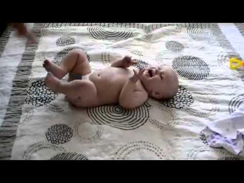 Малыш смеется над мамой с памперсом