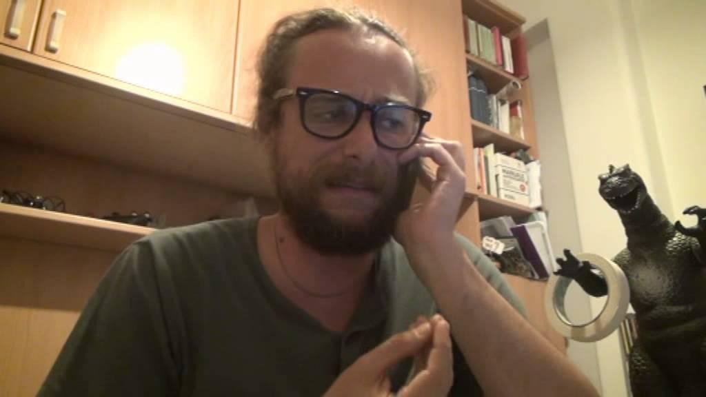Pinuccio al telefono capelli lunghi malamente raccolti dietro barba incolta media è al telefono e sullo sfondo si vede una libreria e l'inconfondibile dinosaurp